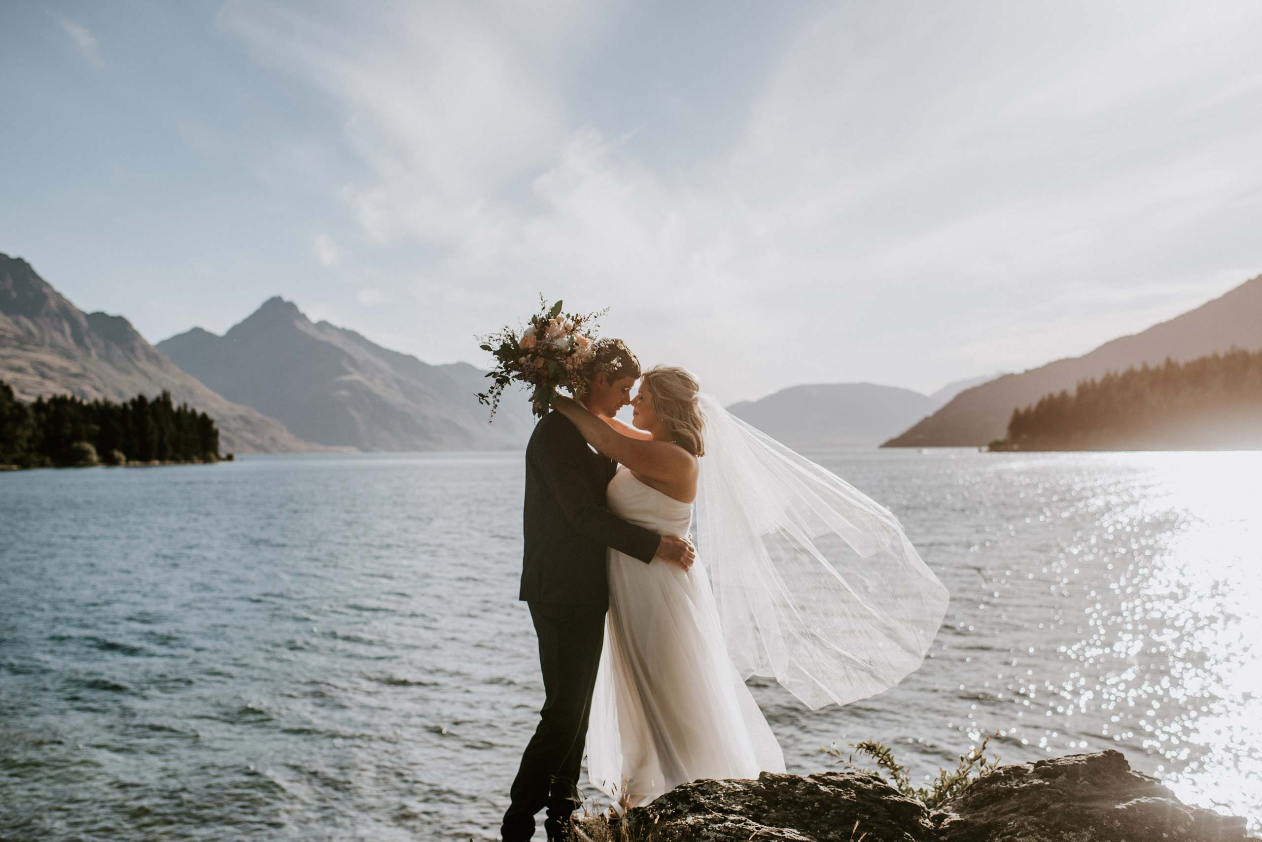 Wedding couple embracing by the lake - Queenstown Wedding Packages